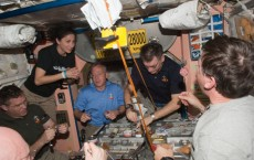 crew members share a meal in the Unity node of the International Space Station.